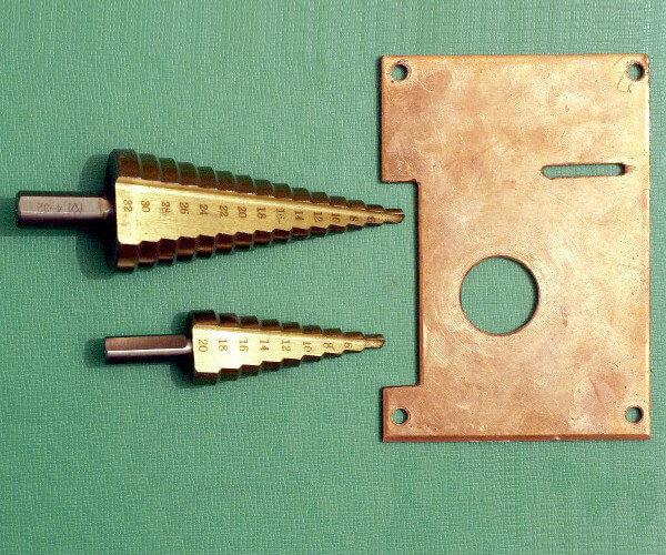 Stufenbohrer für Metall und ein kupferner Gehäusedeckel mit 20 mm Bohrung